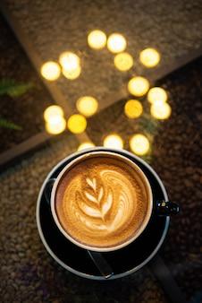 Latte-kunstkoffie met bokeh van lichten op lijst, donkere toon