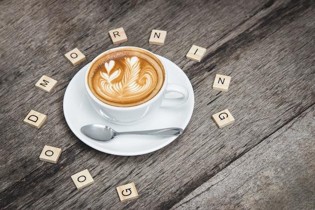 Latte-kunstkoffie met houten woord goede moring ontspant binnen tijd