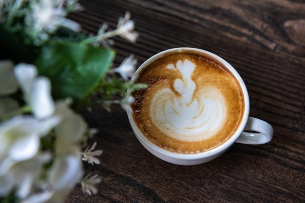 Latte-kunstkoffie op houten lijst met bloemenvoorgrond