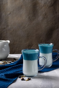 Latte matcha dalgona. hete verse melk met blauwe vlindererwtenbloemen. op een lichtgrijze tafel. verticale oriëntatie