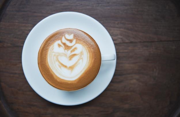 Latte of cappuccino met schuimig schuim, koffiekopje bovenaanzicht op tafel in café.
