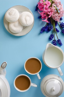 Latte, witte schuimgebakjes, melkkruik op pastelkleur blauwe die achtergrond met muscari en hyacintbloemen wordt verfraaid.