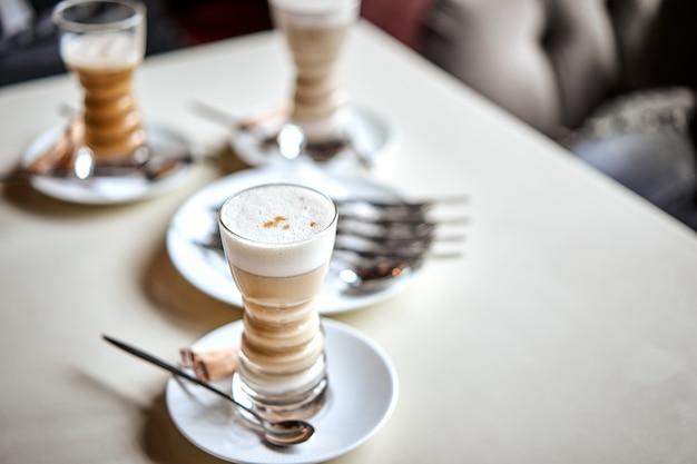 Latteglas met gelaagde latte, cappuccino of mokka met schuim op tafel in café met melkschotel en lepel. drie kopjes koffie.