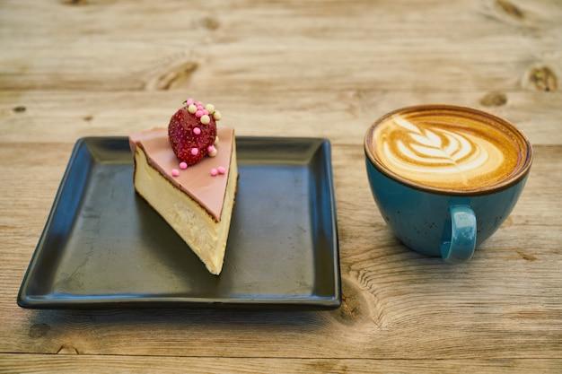 Lattekoffie en kaastaart op de houten lijst