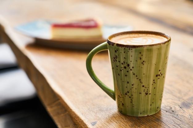 Lattekoffie en kaastaart op een lijst