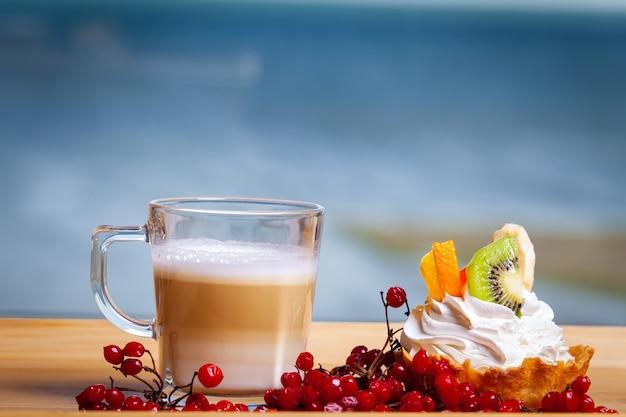 Lattekoffie in glas met een heerlijk dessert met vers fruit en room de zee op de achtergrond