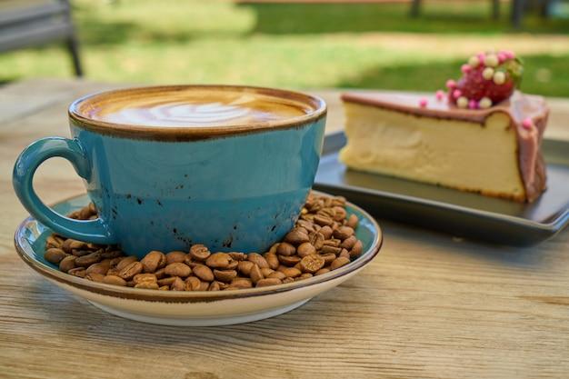 Lattekoffie, koffiebonen en kaastaart op de houten lijst