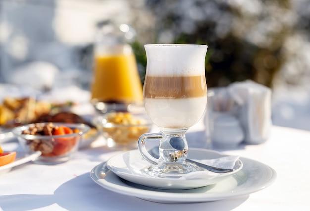 Lattekoffie op het terras voor het restaurant tegen de sneeuw
