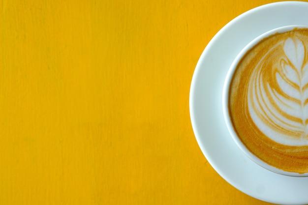 Lattekunstkoffie in een wit tegelglas op een gele lijst