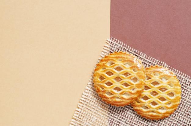 Lattice bedekte gebakjes met een appelvulling op jute