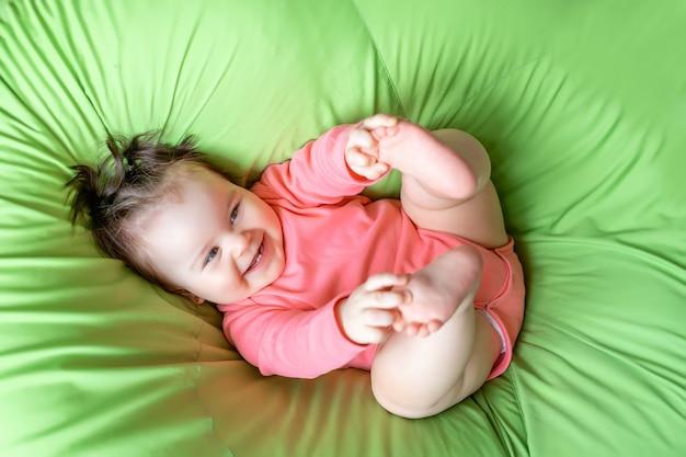 Laughing baby in roze kleren op een groene deken thuis