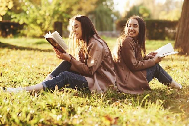 Laughinh brunette tweeling meisjes rug aan rug zitten op het gras en plezier met benen licht gebogen in knieën, met bruine boeken in handen, casual jas dragen in herfst park op onscherpe achtergrond.