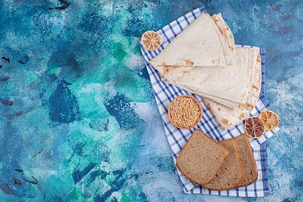Lavash en gesneden brood op een theedoek, op de blauwe tafel.