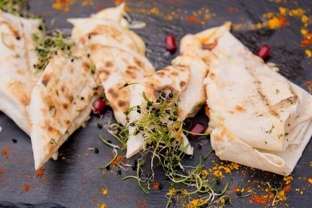 Lavash met kaas op een plat zwart bord versierd met microgroen en granaatappelpitjes. restaurant gerecht.