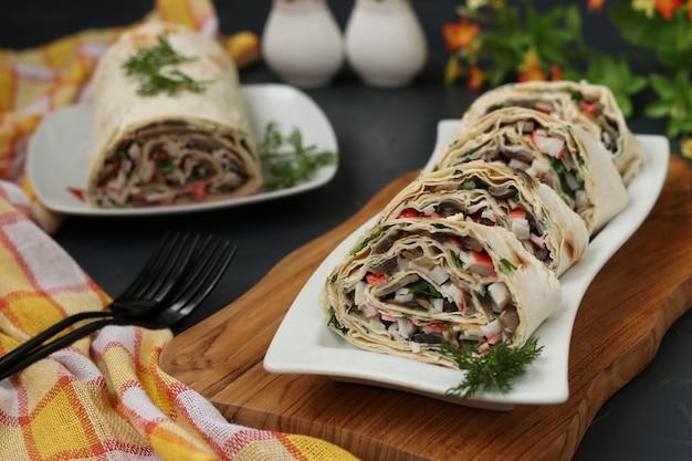 Lavashbroodje met champignons, krabstokken en kaas, feestelijk voorgerecht, close-up, horizontaal formaat