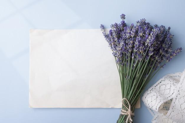 Lavendel bloemen in een boeket met blanco vel oud papier voor tekst en lihgt uit raam op tafel