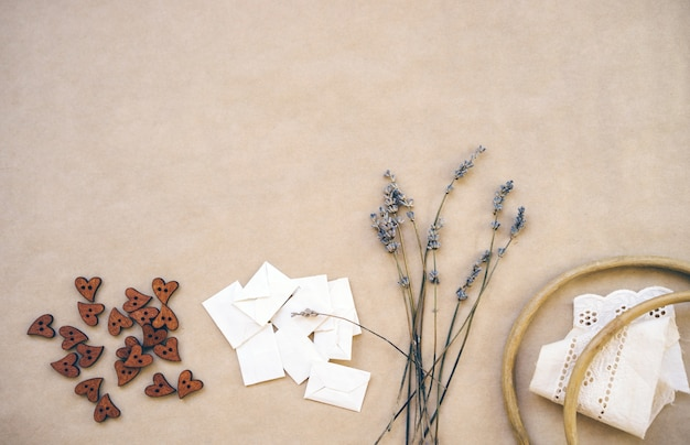 Lavendel, houten knopen, zelfgemaakte enveloppen, oude houten hoepel en linten met zoom op ambachtelijk papier.