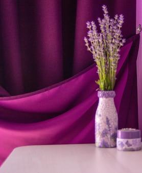 Lavendel in de vaas op tafel. purper gordijn en violette muurachtergrond.