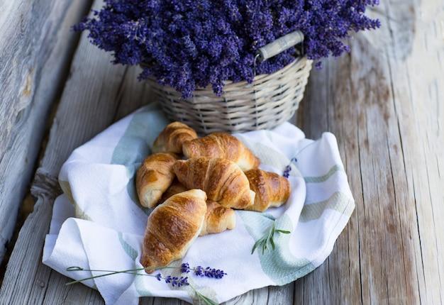 Lavendel in een mand en croissants op een tafelkleed op een houten tafel (close-up)