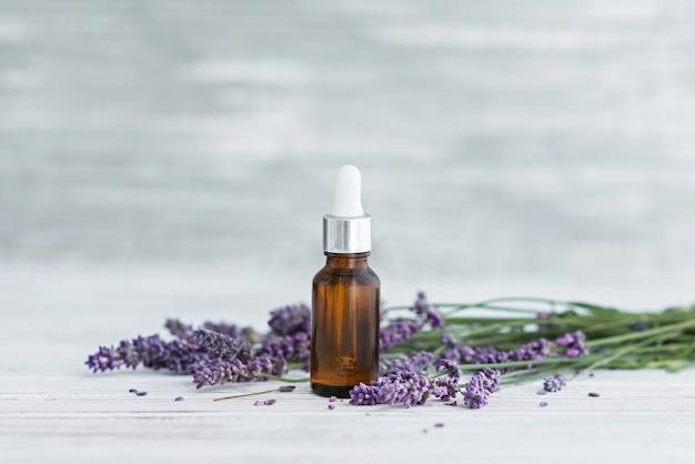 Lavendel kruidenolie en lavendelbloemen op grijze houten achtergrond.