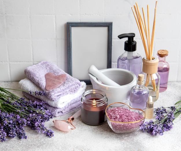 Lavendel kuuroord. etherische oliën, zeezout, handdoeken en gezichtsroller. natuurlijke kruidencosmetica met lavendelbloemen
