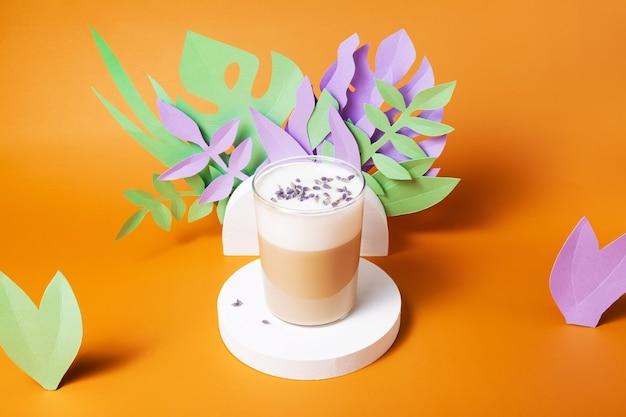 Lavendel latte-drank op ronde standaard omringd door verschillende papieren bladeren