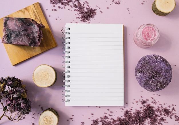 Lavendel zeep bar; houten stronk; body scrub; gedroogde bloem en enkele pagina notitieblok op roze achtergrond