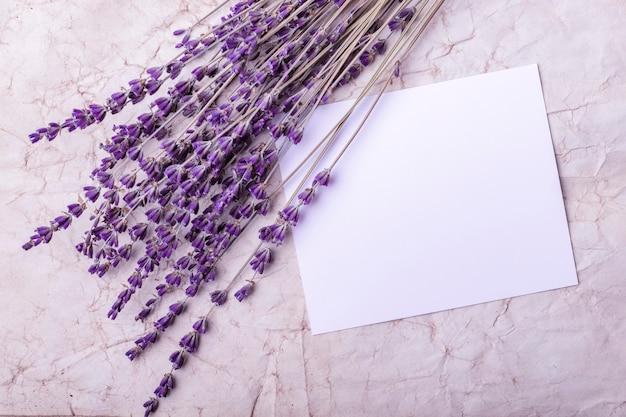 Lavendelbloemen en blanco papier op de achtergrond van oud papier. kopieer ruimte. versteviging