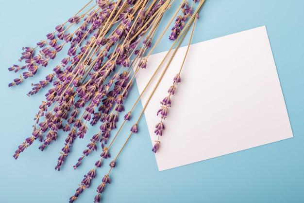 Lavendelbloemen en blanco papier op een blauwe achtergrond. kopieer ruimte
