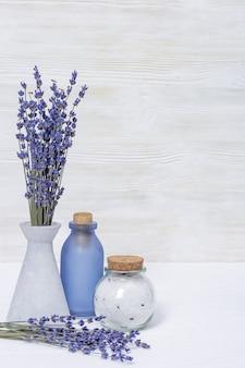 Lavendelbloemen en glazen flessen, geurig zeezout. kuuroordconcept met exemplaarruimte.