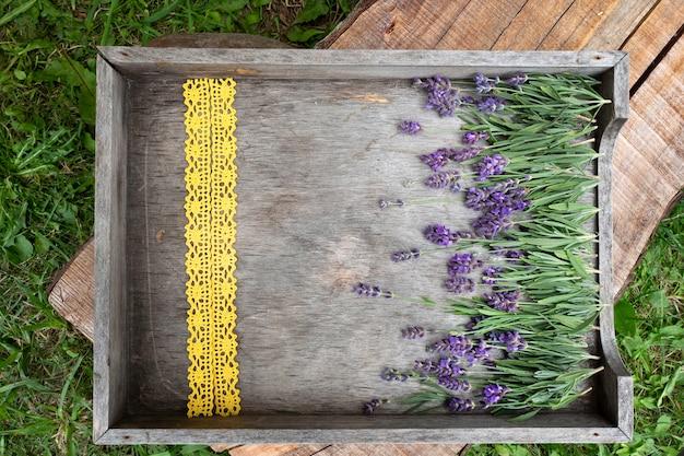 Lavendelbloemen en olie op een houten geweven doos