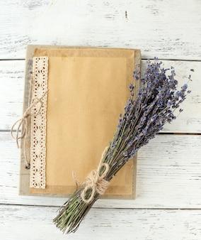 Lavendelbloemen en oud fotoalbum op houten tafel