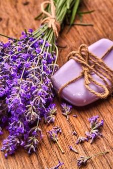 Lavendelbloemen halen kuuroordzeep en bos van lavendelfloawers op houten raad uit