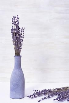 Lavendelbloemen in blauwe glazen fles, kuuroordconcept, aromatherapie, exemplaarruimte