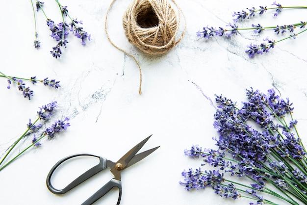Lavendelbloemen, schaar en touw op een wit marmer