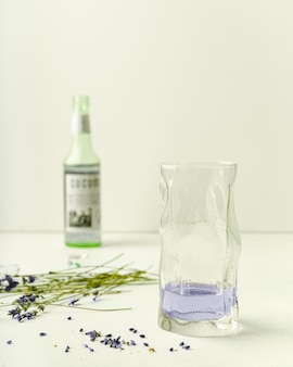 Lavendellimonade in longdrinkglas, fles, droge lavendelbloemen