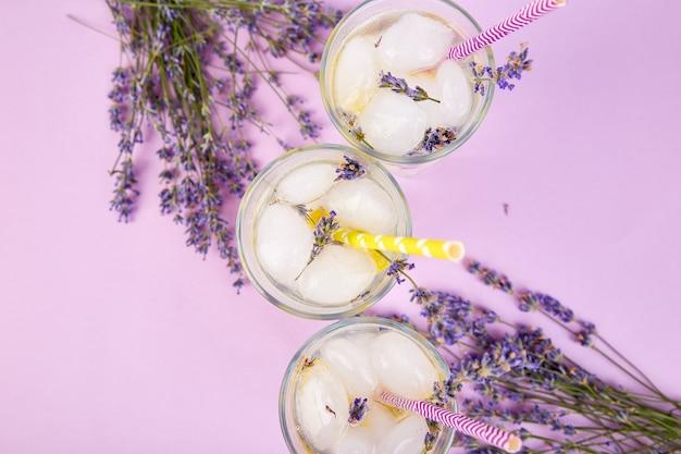 Lavendellimonade met citroen en ijs op purpere achtergrond.