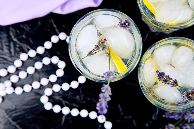 Lavendellimonade met lemonndijs op zwarte.