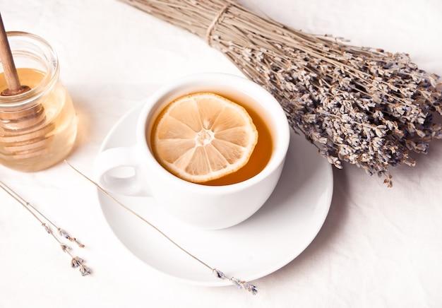 Lavendelthee met citroen en honing op de lichte achtergrond