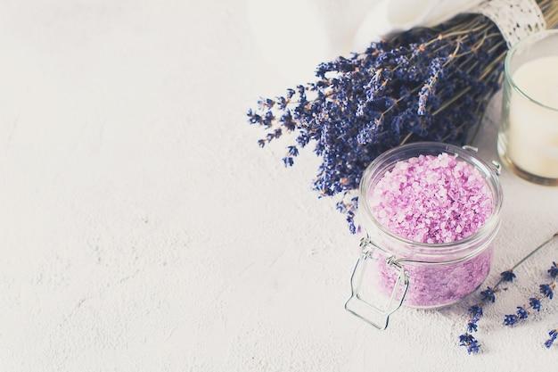 Lavendelzout met natuurlijke kuuroordproducten en decor voor bad op grijze achtergrond