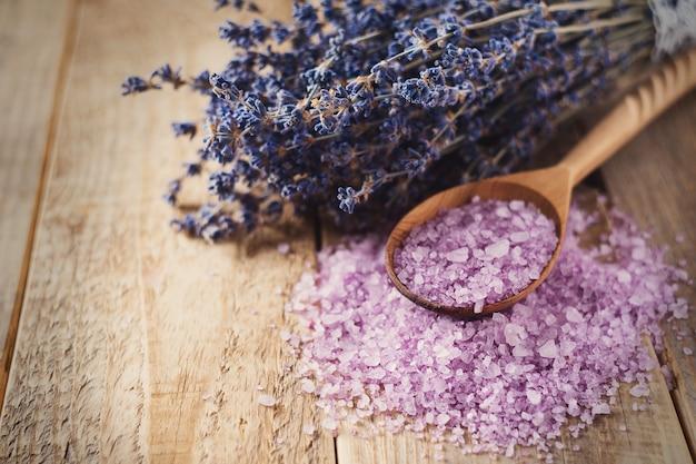 Lavendelzout met natuurlijke kuuroordproducten en decor voor bad op houten achtergrond