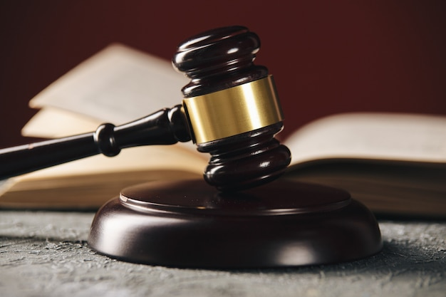 Law concept - open wet boek met een houten hamer van de rechters op tafel