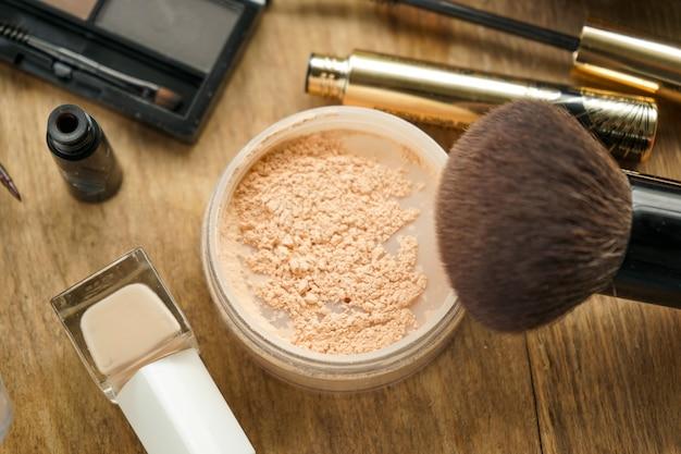 Lay-out, een set damescosmetica, licht poeder met een grote borstel, wenkbrauwschaduw met een borstel, zwarte mascara, beige nagellak, bruine eyeliner