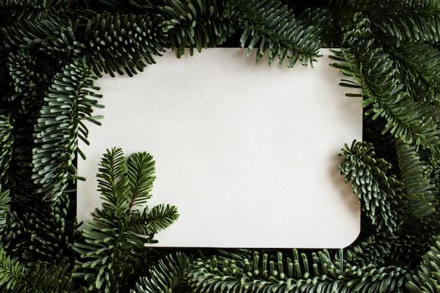 Lay-out gemaakt van kerstboomtakken met witte papieren kaartkopieer ruimte voor tekstplatte lay-stijl