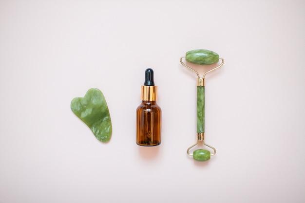 Lay-out met jade gezichtsmassageapparaat en serumfles op lichtroze