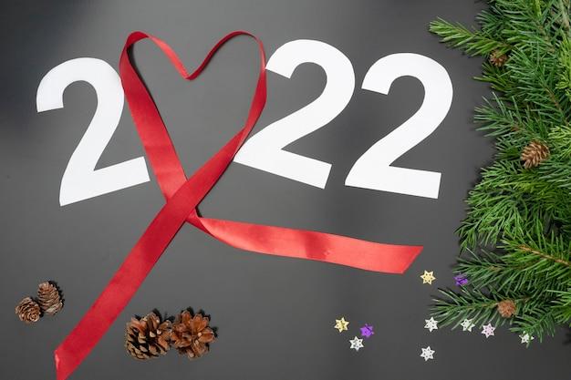 Lay-out op het thema van de nieuwe 2022 met een rood lint, speelgoed en takken van een kerstboom op een donkere achtergrond.