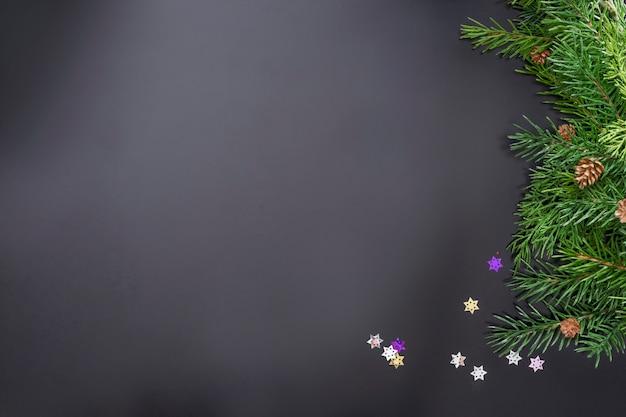 Lay-out op het thema van de nieuwe 2022 met speelgoed en takken van een kerstboom op een donkere achtergrond.