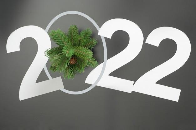 Lay-out op het thema van het nieuwe jaar 2022 met cijfers en takken van een kerstboom op een donkere achtergrond.