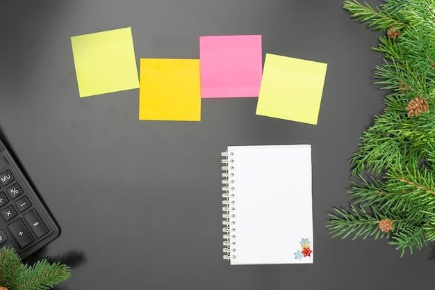 Lay-out op het thema van het nieuwe jaar 2022 met een notitieboekje, kleurrijke notities, een rekenmachine, speelgoed en takken van een kerstboom op een donkere achtergrond.