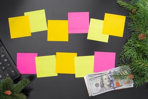 Lay-out op het thema van nieuwjaar 2022 met kleurrijke notities, rekenmachine, geld, speelgoed en takken van een kerstboom op een donkere achtergrond.